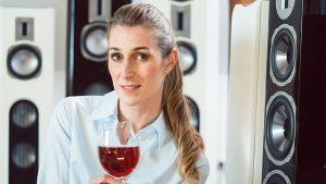 ドリンクと音楽を楽しむHi-Fiスピーカーの前でワインを飲む女性の画像